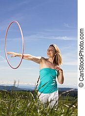 Blond mature womanplays with hula hoop - Blond woman...