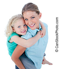 Blond mother giving her daughter piggyback ride against a...