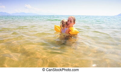 Blond Mother Holds in Arms Little Daughter in Azure Sea