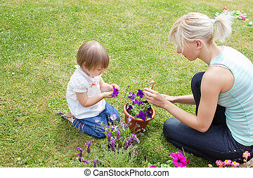 Blond Mother showing her daughter a purple flower