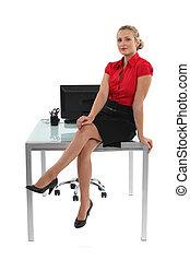 Blond office worker sat on her desk