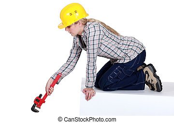 Blond plumber using adjustable wrench