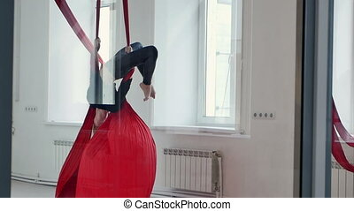 Blond pole dancer exercising on aerial fabric. Slow motion. ...