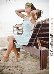 blond pretty girl relaxing sitting on bench outdoors on light copy space seaside background portrait