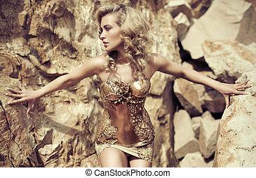 Blond pretty woman among the rocks