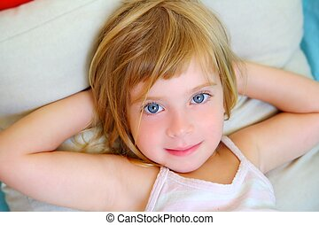 blond relaxed girl on pillow blue eyes smiling looking...