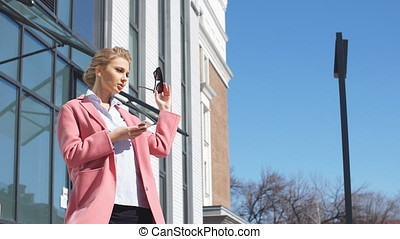 Blond serious woman calling on smart phone.