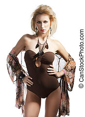 blond sexy beautiful young woman wearing a flower scarf over her body with brown swimsuit with jewellery, she is in front of the camera, looks in to the lens and has both hands on her hips