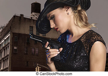 Blond sexy girl with handgun pistol gangster style