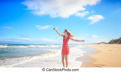European blond long-haired slim girl in red dress barefoot circles on wet sand beach makes selfie against wave surf