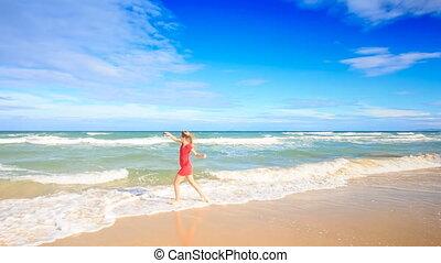 Blond Slim Girl in Red Runs into Surf Makes Selfie