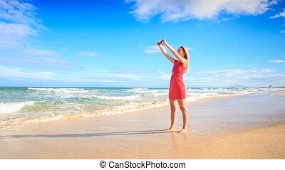 Blond Slim Girl Jumps on Beach Makes Selfie in Red Barefoot
