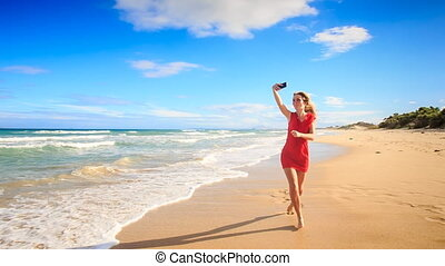 Blond Slim Girl Runs along Beach Makes Selfie in Red Barefoot