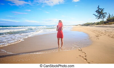 Blond Slim Girl Walks along Surf Hides Face with Red Heart