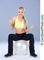 Blond sporty woman sitting on fitness ball