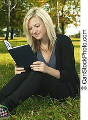 blond student girl reading book on grass