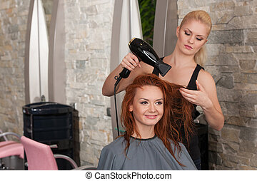 blond stylist drying redhead woman hair in salon. happy female giving new hair style to woman at parlor