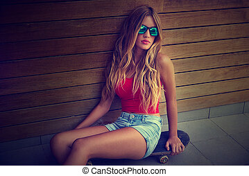 Blond teen girl sit on skate in a wood wall - Blond teen...