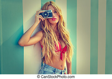Blond teen girl with vintage photo camera