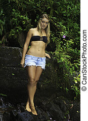 blond teenage girl in a tropical forest