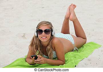 Blond teenager at the beach listening to music