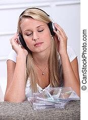 Blond teenager listening to music through headphones