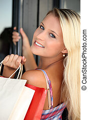 Blond teenager with shopping bags