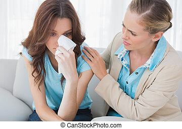 Blond therapist looking at her patient crying