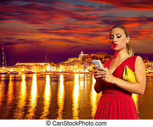 Blond tourist girl smartphone chat in Ibiza sunset