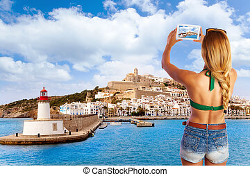 Blond tourist photo tablet pc in Ibiza skyline