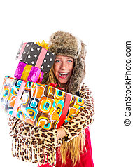 Blond winter kid girl with stacked presents smiling