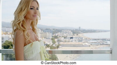 Blond Woman Admiring City View from Balcony - Attractive...