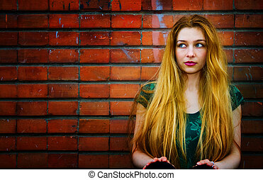 Blond woman and brick wall