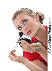 Blond woman applying blusher