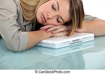 Blond woman asleep on laptop