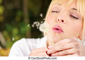 Blond woman blowing flower