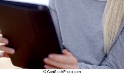 Blond Woman Busy with her Tablet Device