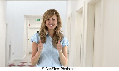 Blond woman celebrating a good news in the school corridors...
