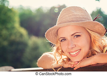 Blond woman, curly hair in green nature. Sunny summer -...