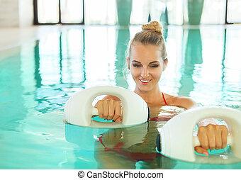 Blond woman doing aqua aerobics with foam dumbbells in swimming pool