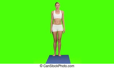Blond woman doing exercise against a green screen