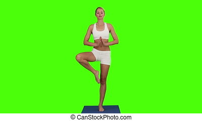 Blond woman doing yoga on her ground cloth