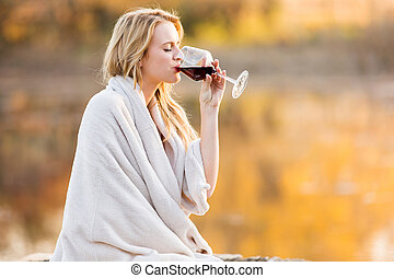 blond woman drinking red wine at sunset