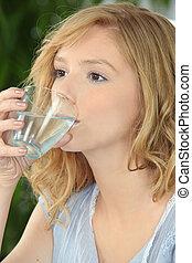 Blond woman drinking water