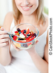 Blond woman eating a fruit salad