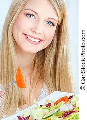 Blond woman eating salad