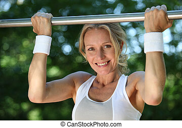 Blond woman exercising on pull-up bar outdoors