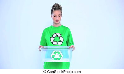 Blond woman giving a recycling box to the camera on white...