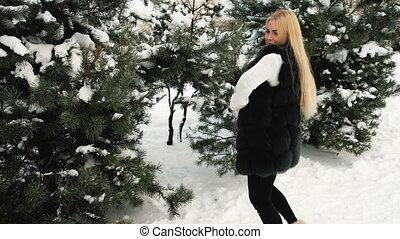 Blond woman has fun, jumps in fir-tree winter forest outdoors