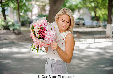 Blond woman holding a beautiful composition of flowers